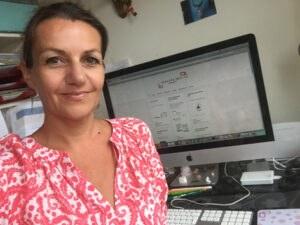 Astrid Stockinger lächelnd vor dem PC im Büro